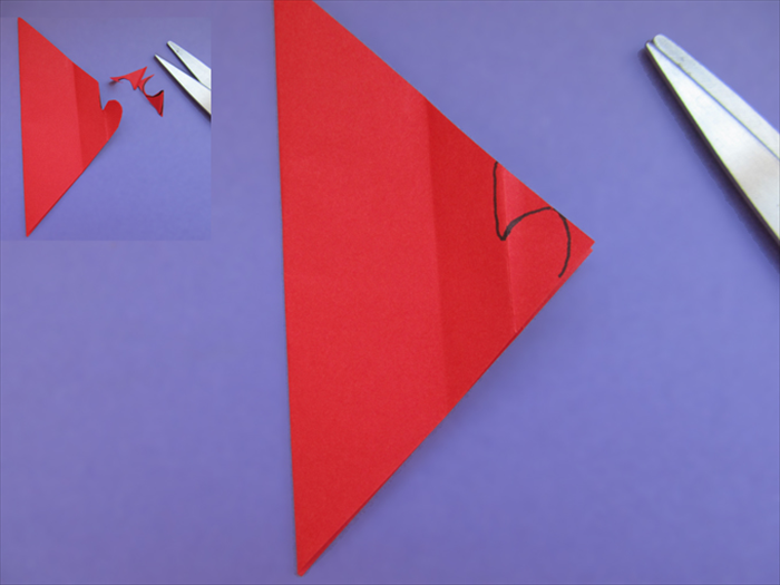Cut out a half heart When you get to the top of the heart,  cut a straight line up *a tiny bit to the left of the fold.