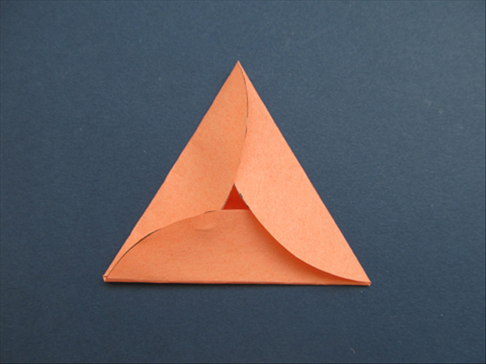 Unfold and remove the scrap paper triangle. Refold along the creases of the triangle and overlap the right side of each corner.   Your Purim card in the shape of a Hamantaschen cookie is folded!  Unfold, write your message inside, refold and add your message on the outside.