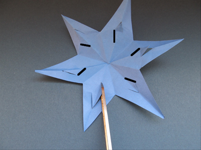 Unfold the star. Push the slits forward.   Make a cut from the right edge to the center crease of each of the 6 slits. Do not cut the left side.