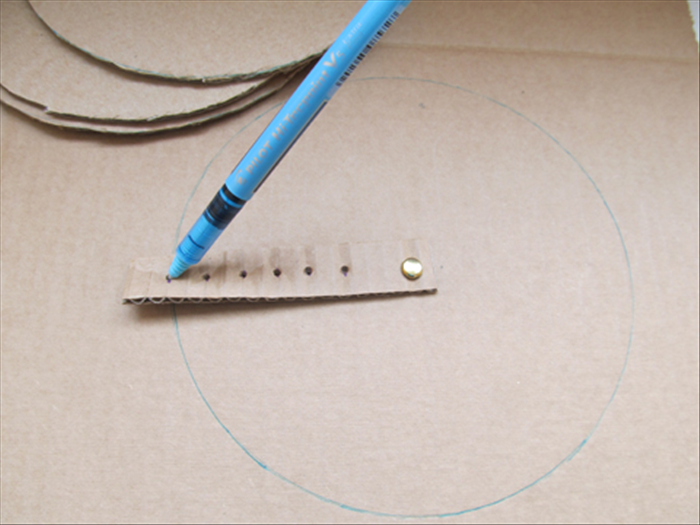 <p> Make a hole in the cardboard with the nail.</p>  <p> Push the paper fastener through the 1 st hole and the hole in the cardboard.</p>  <p> Fasten it in the back.</p>  <p> Put the pen point in the last hole and rotate the strip to draw a circle.</p>  <p> This is the largest circle and the base of the tree.</p>  <p> Make 3 more. Cut out all 4 circles.</p>  <p>  </p>