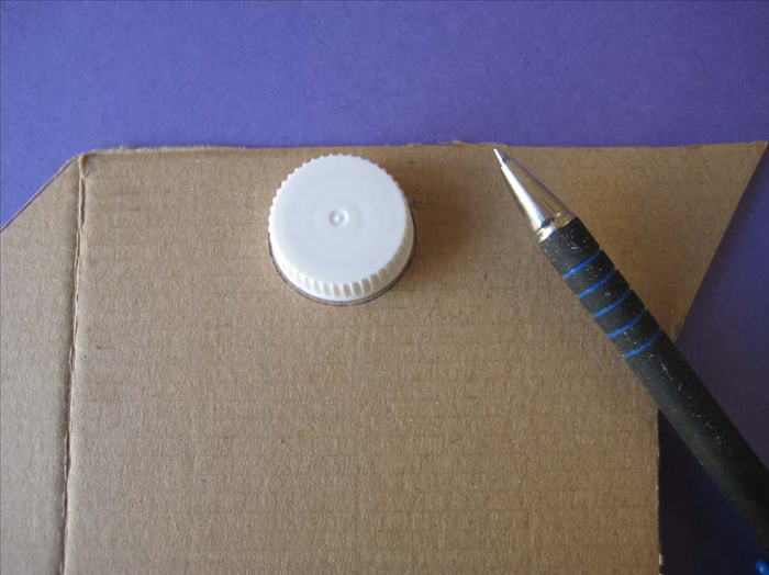 Draw a circle around the small bottle cap on the cardboard.