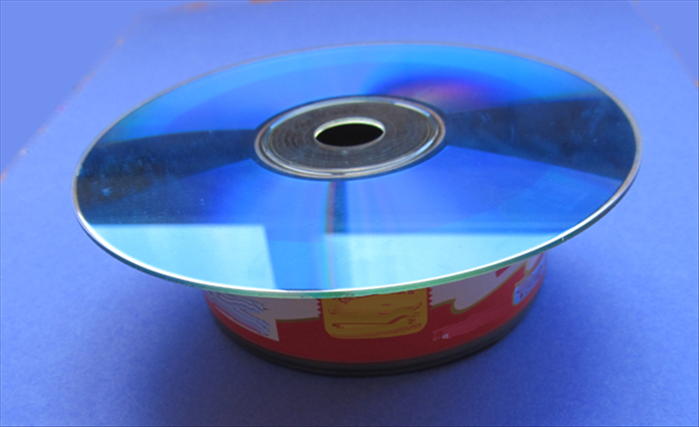 Place the CD on top of the open end of the tuna can