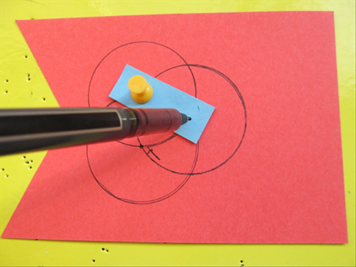 Put the pin in one of the holes on the strip and through the hole you just made on the paper. Put the pen point in the second hole and rotate it to draw another circle.