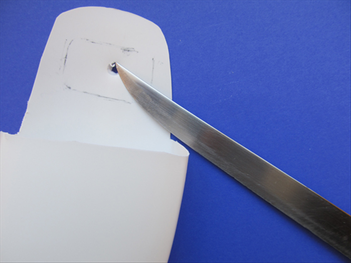 Use a sharp point to punch a hole in the center of the outline. The hole should be big enough for your scissor to go through.