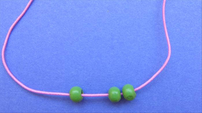 String 3 green beads to the middle of the string.