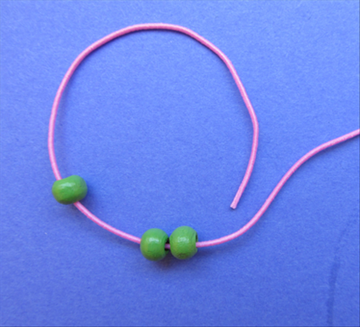 Take the left end of the string and insert it into and through the 2 beads from the right side.