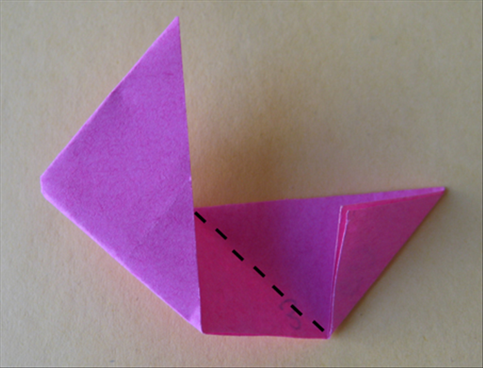 <p> Fold the right side down to the center crease so that it aligns with the flap you just made.</p>