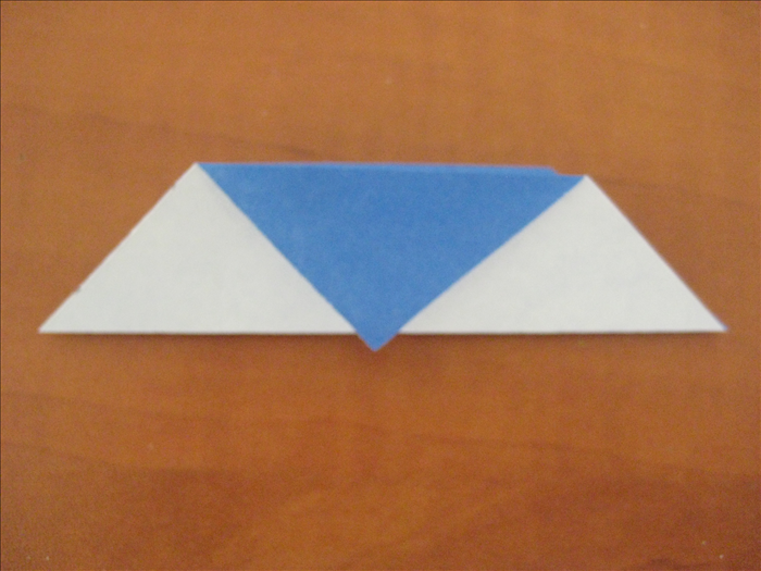Fold the paper  in half by bringing the bottom edge up to top edge