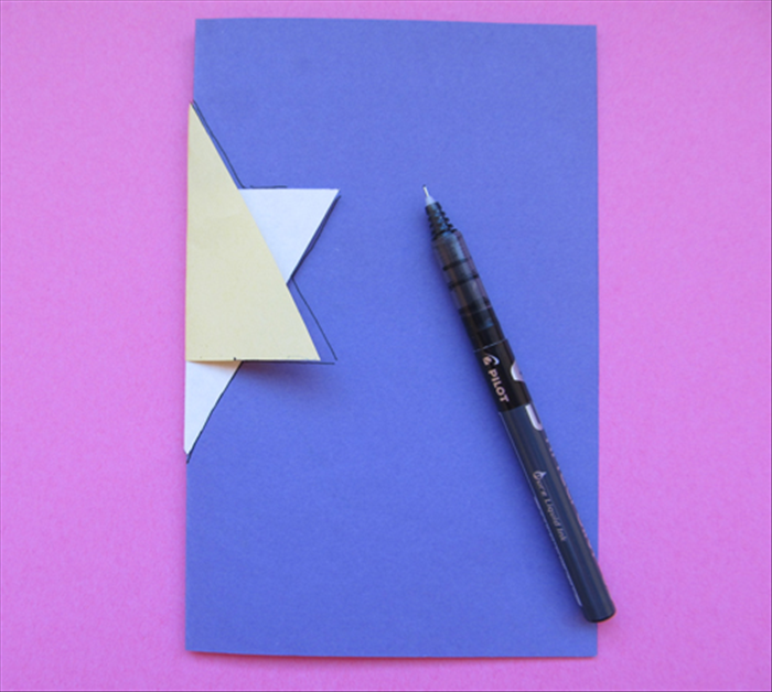 <p> Fold the 7 X 9 inch paper in half.  Insert the folded edge into the folded star.</p>  <p> Trace the half star. You only need to trace it on the one side of the folded paper.</p>