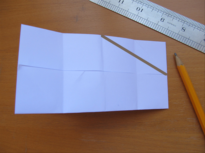 Fold the paper in half. There should be 8 squares and the flaps  facing inside Draw a line from the center of the top to the center of the right side