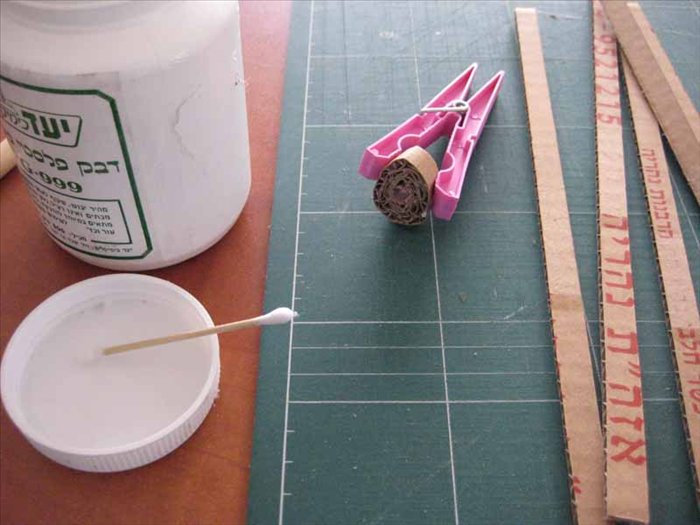 Coat one side of a strip with glue and roll it up tightly. Hold it together with the clothespin until the glue is dry.  Do this for 10 strips of coardboard