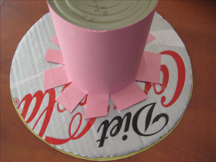 Tape the tabs sticking out from the can to the underside of the cardboard circles you just covered