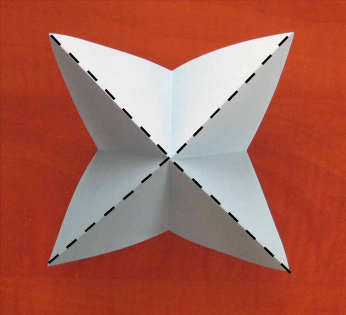 Flip the paper over to the other side. Pinch  all the diagonally folds. Continue to squeese them and the horizontally folds will fold inward.