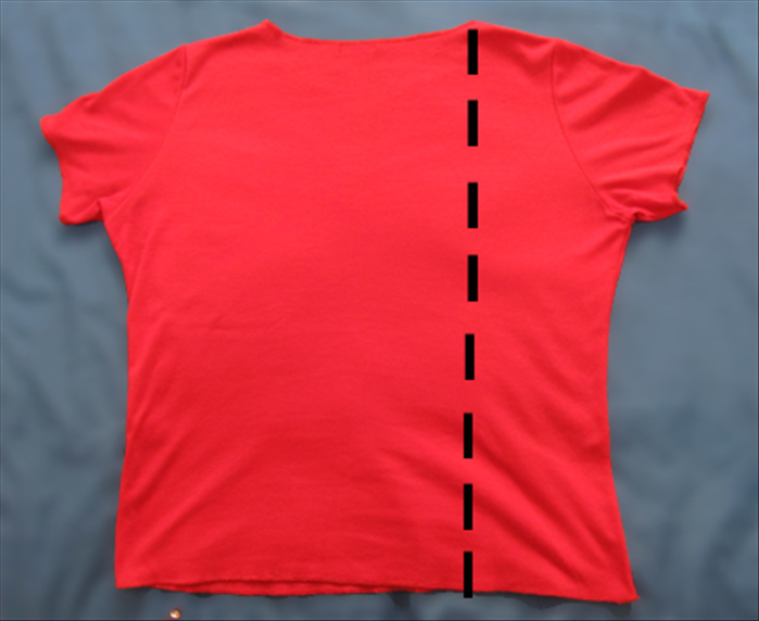 Spread the tee shirt with the front facing down Fold the right side from the right edge of the neckline