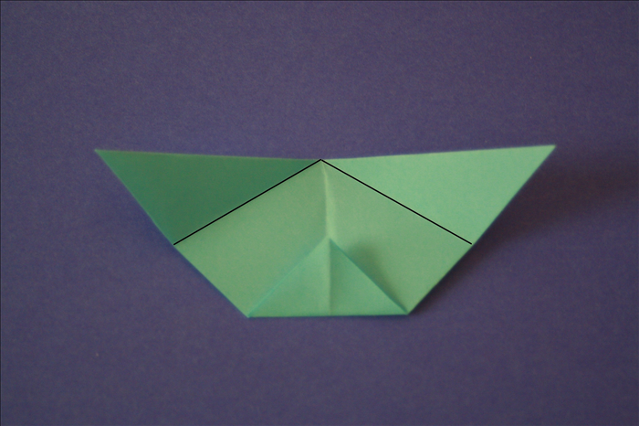 Fold the top corners down at an angle until they touch the corners of the triangle at the bottom