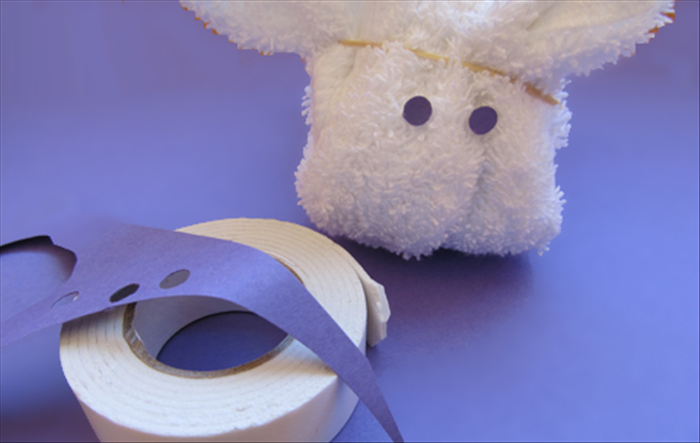 Use a hole puncher to cut out 2 circles for the eyes Cut a tiny tip off of the edge of the 2 sides tape to attach the circles to the bunny