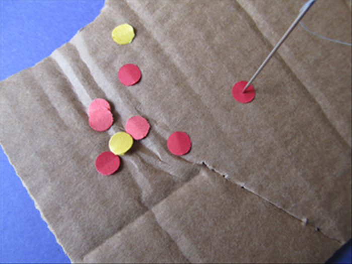 Place circles on the corrugated cardboard. Punch the threaded needle as close to the center of the circles as you can.