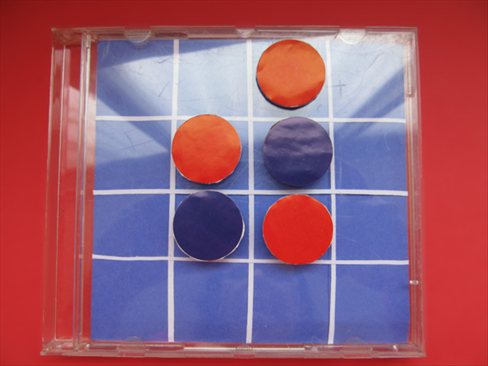 Each player chooses a color. To play the game you place your color in an empty square so that one or more of your opponent's pieces is between your pieces.  In this picture the red is on the top and bottom of the blue.