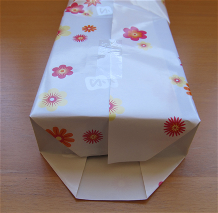 Push down the paper along the top edge of the gift.