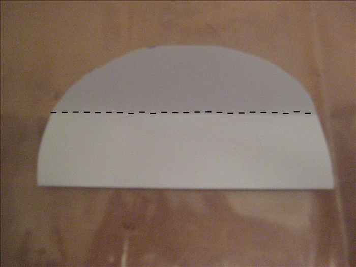 Bring the bottom edge up to the top to fold the circle in half again