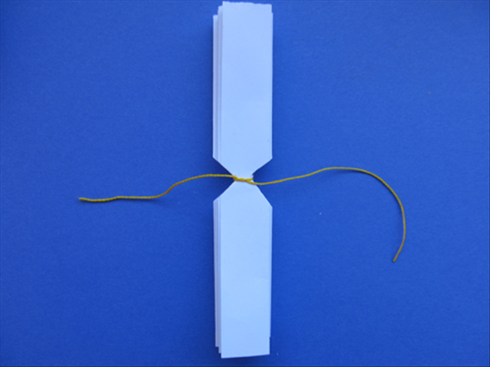 Tie a string around the paper at the cut area on both papers