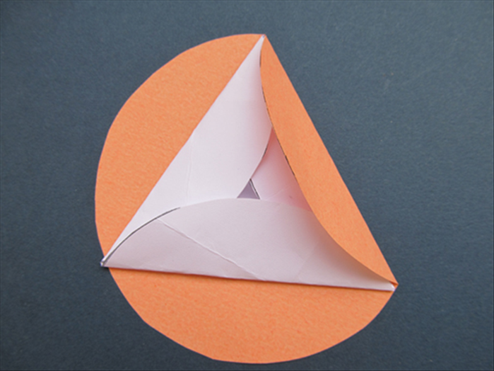 Fold one side up over the edge of the triangle