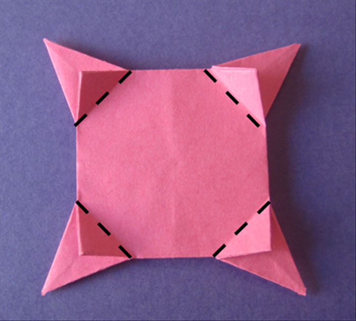 Flip the paper over to the back side. Fold the small flaps towards the center.