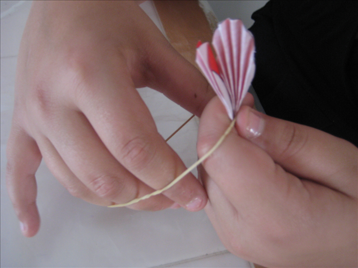 Hold the folded circles together and wrap a rubber band or string around the center to hold them in place.