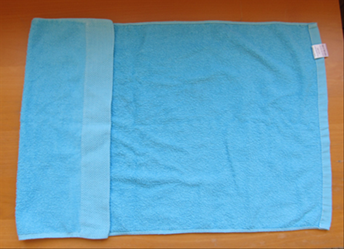 Open up the towel with the short edges at the sides.