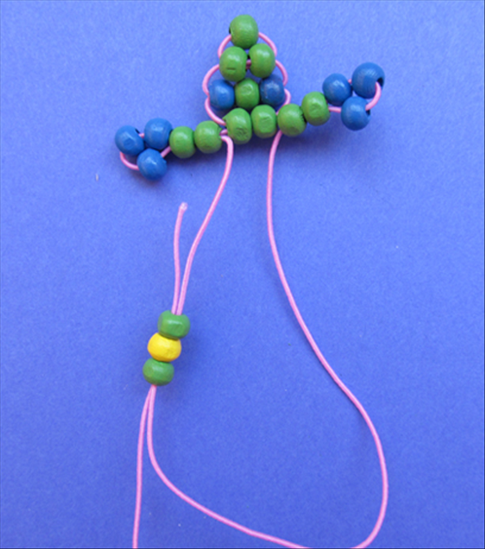 Insert the right string through the bottom of the beads. This is the same procedure used for every row (besides the legs). 