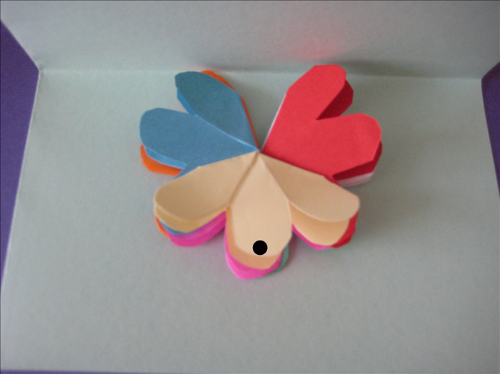 Fold you card in half.  Lift up one side of your card. Place a dot of glue on the middle petal on the front and  the middle petal on the back- you are placing glue only where they touch the card.  Align the flower to the center crease of the card.  Close the card and press down Wait for the glue to dry completely