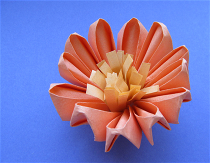 Hold the flower with the face up. Insert the uncut end through the hole in the center.  Your Paper Kanzashi Flower is finished!
