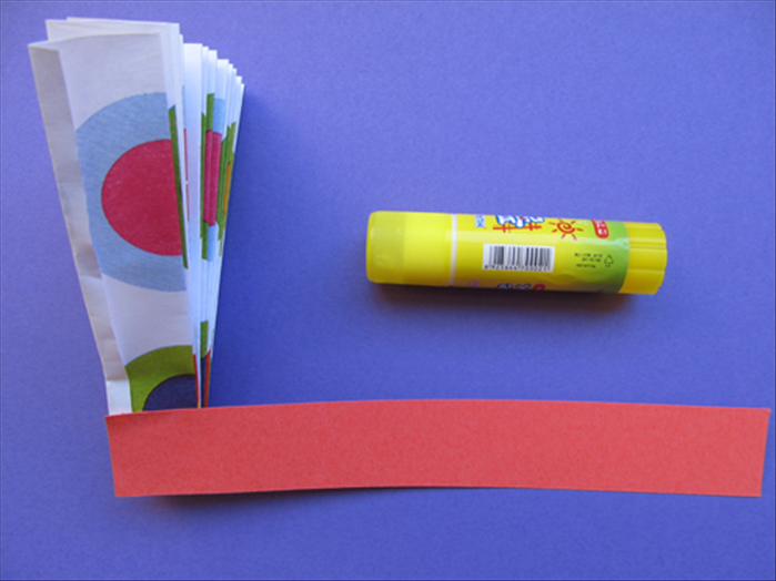Align the small strip of paper with the side and bottom of the folded paper Glue it in place