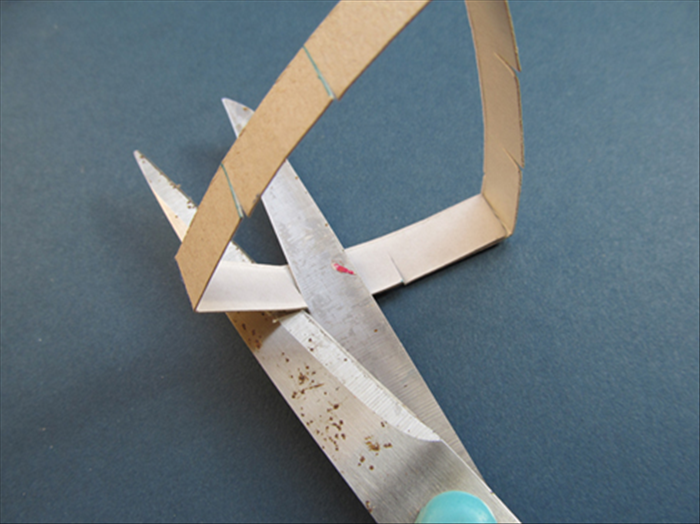Use the present cuts as a guide.Cut again to make a cut on the overlapping cardboard.