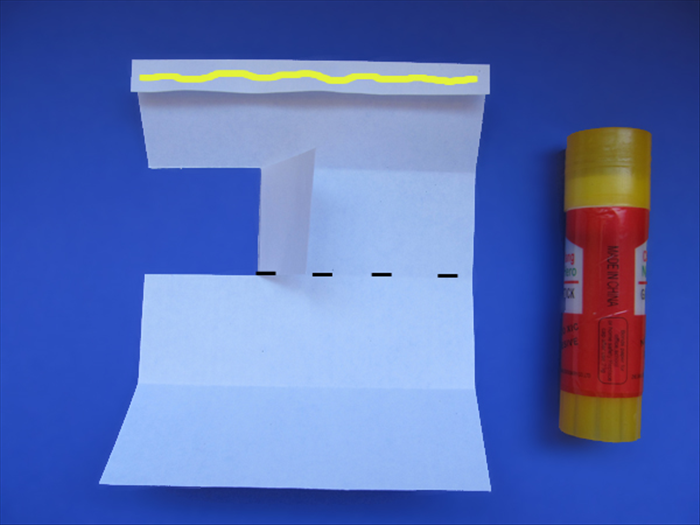 <p> Flip the paper over. The folded edge should be on top.</p>  <p> &nbsp;</p>  <p> Fold the flap over.</p>  <p> Put glue on the folded edge.</p>  <p> Bring the bottom edge up to the top edge to fold the paper in half.</p>   <p> Let the glue dry.</p>   <p> &nbsp;</p>