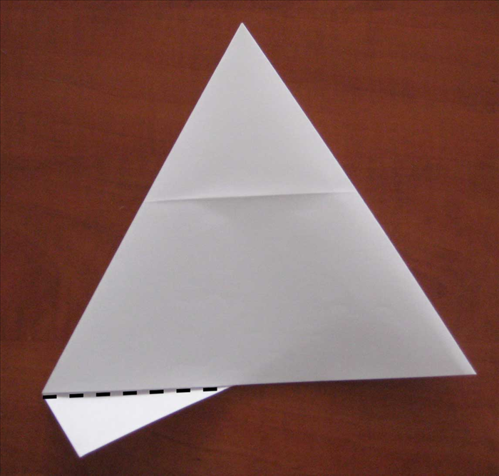Flip the paper over to the back side. Fold the small piece sticking out at the bottom over the edge. Unfold it and then refold it but stick it in between the layers.