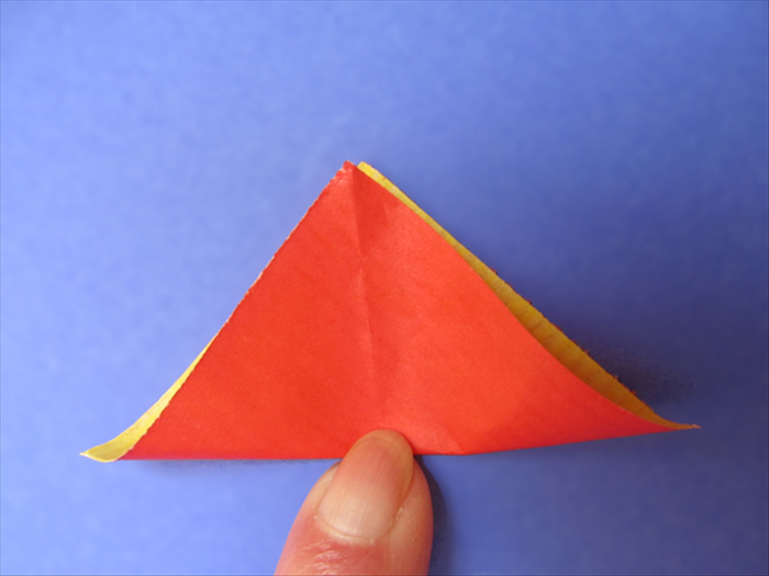 <p> Bring the bottom point up to the top as if you were going to carefully fold it in half.</p>  <p> Do not fold it. Pinch at the center.</p>  <p> Unfold</p>  <p>  </p>
