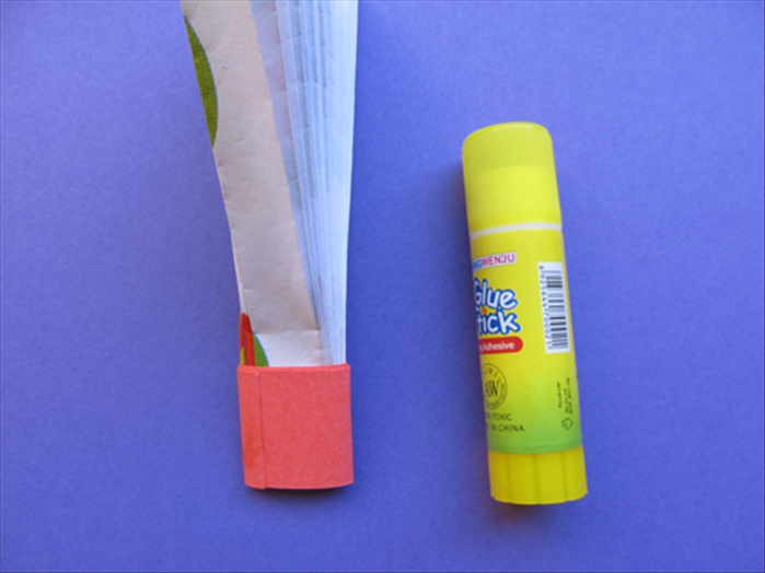 Wrap the strip around the bottom of the folded paper and glue the end closed