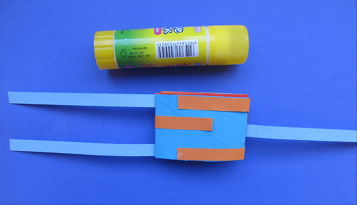 Bring the strips from the bottom tube up and over and to the opposite side. Glue them in place.