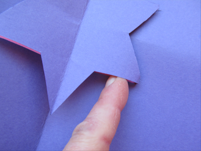 <p> Open up the card and stick your finger under the star to fold the parallel lines down from the bottom.</p>  <p> Lift the star to push it up from the middle and squeeze the center crease so it will go in the other</p>  <p> direction.</p>  <p> Close the card and give it a sharp crease.</p>