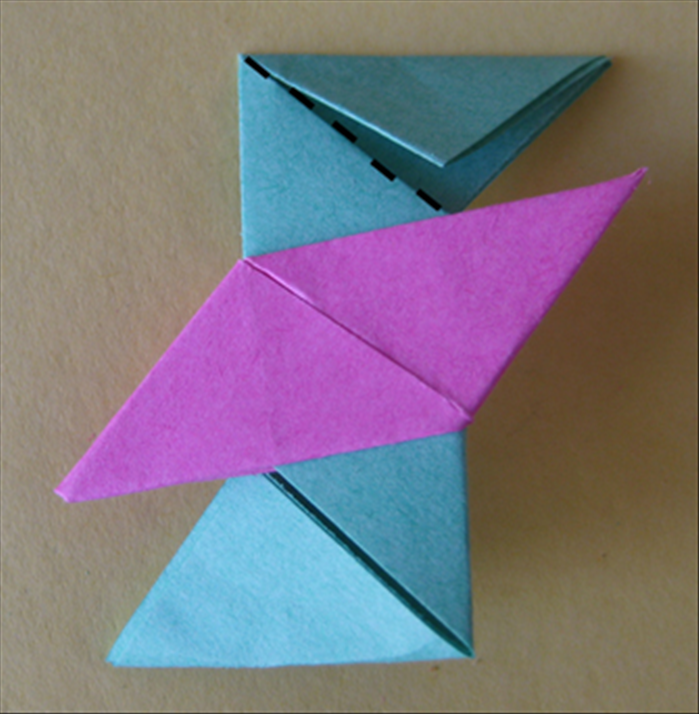 <p> Flip the paper over to the back side. Fold the top down along the flap.</p>