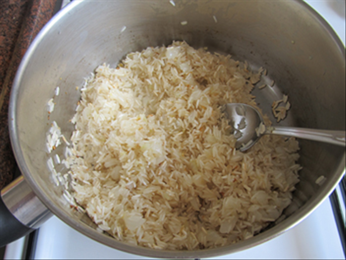 Add the uncooked rice to the pot and stir and fry until it is golden brown