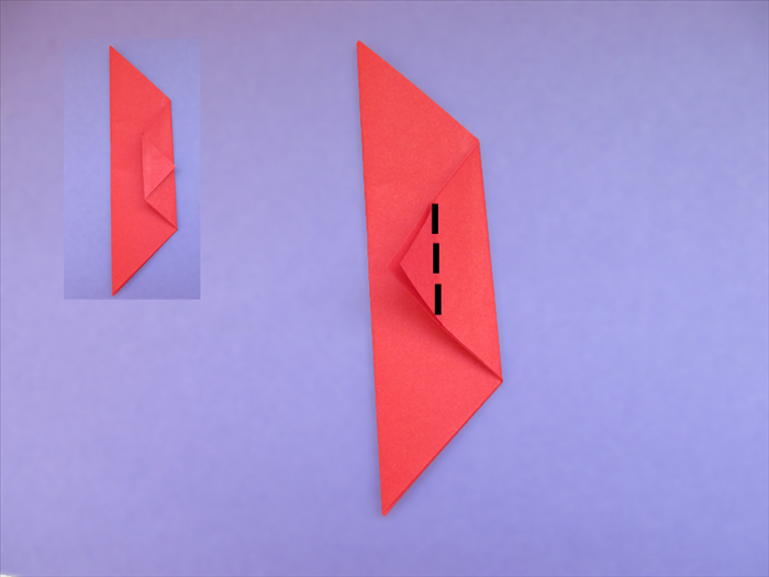 Fold the point to the opposite edge Make a sharp crease and unfold