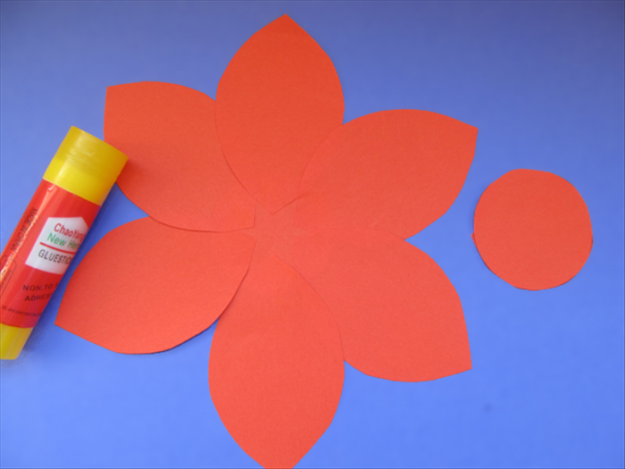 <p> Glue them to the circle with the same side of each petal overlapping.</p>   <p> Glue the second circle to the center.</p>   <p>  </p>