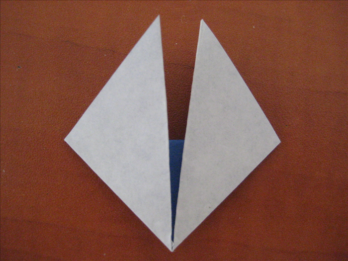 Fold the outer side points upward, along the edges of the middle triangle, to meet in the center. It will create a square