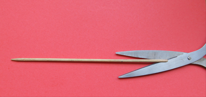 <p> Carefully make a slit in the flat end of the skewer with a scissor.</p>