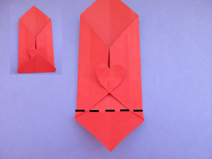 Fold the bottom point up to the top of the heart. Crease and unfold