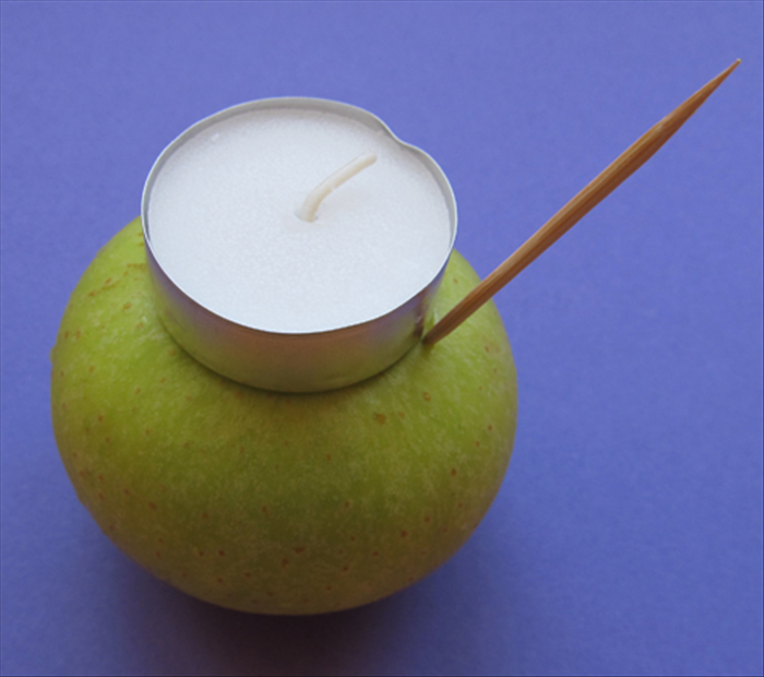 Place the candle on the center top of the apple.  Insert a toothpick at the edge of the candle.  Drag it around the outside of the candle to mark the shape.