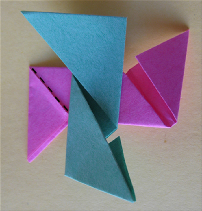 <p> Flip the first paper over to the back side. Rotate the second paper and place it on top of the first in the center as shown in the picture. Fold the paper on the bottom along the flap</p>