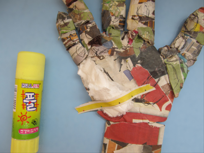 Put glue on one side of newspaper strips. Place them on top of the toilet paper and around the sides.